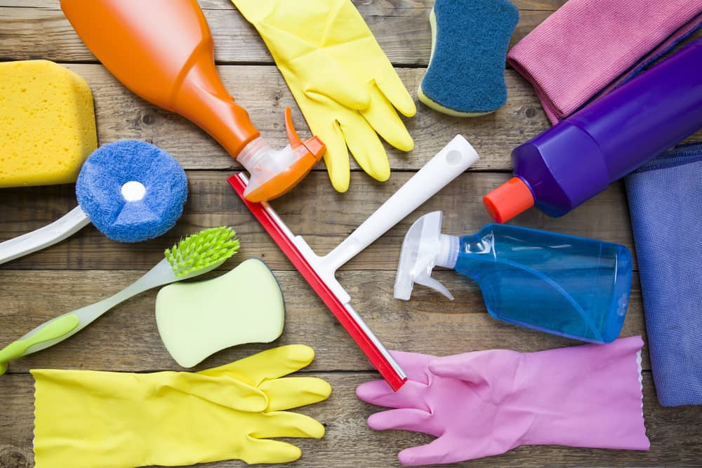 Brushes, rubber gloves, and cleaning supplies to clean a home for the holidays